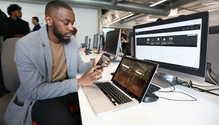 Male student looking at app on phone siting in front of laptop and desktop computers