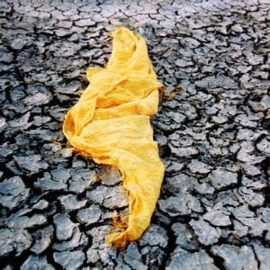 Yellow scarf on dried-up soil.
