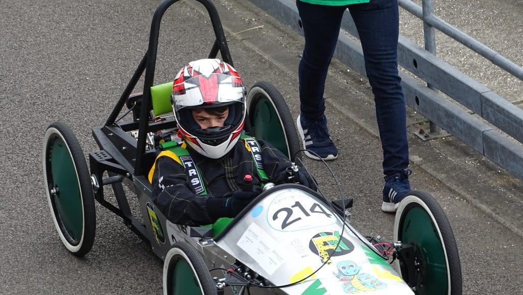 Student sitting in F24 car, wearing a crash helmet