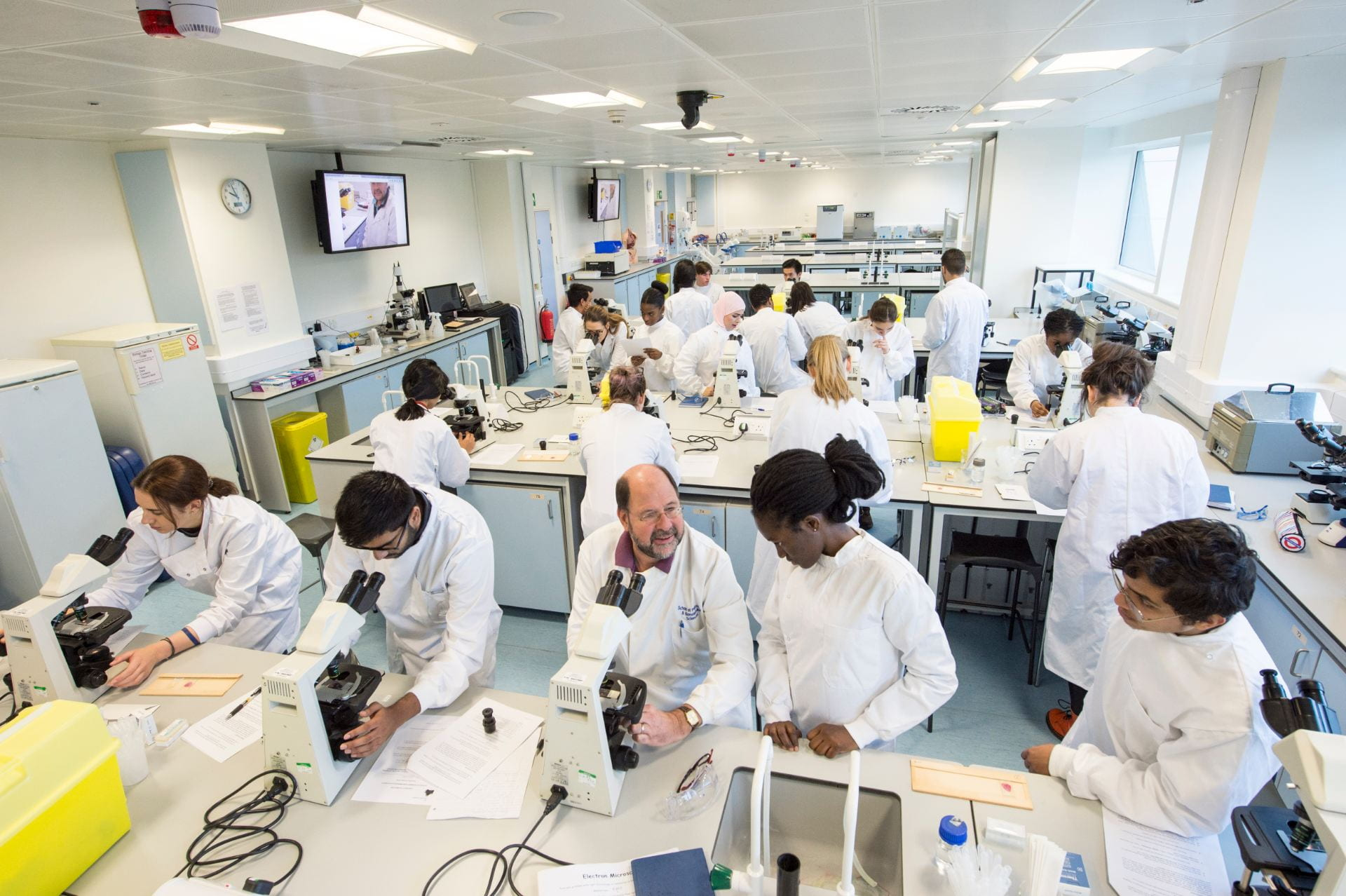 Students in lab coats working in a Microscopy lab