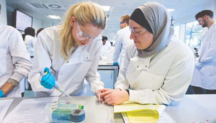 Two female students working in the cell pathology lab