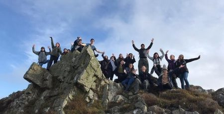 Group of students on top of a rock