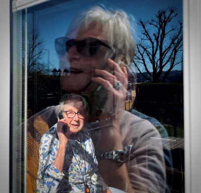 an elderly person talks on the phone
