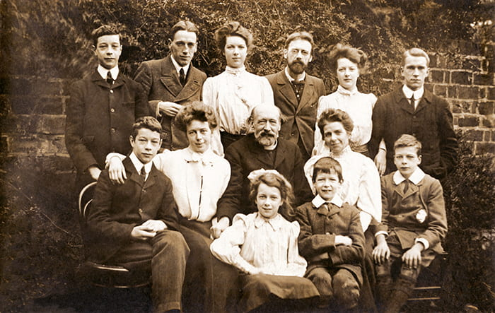 A black and white family portrait showing 13 members of the Gill family