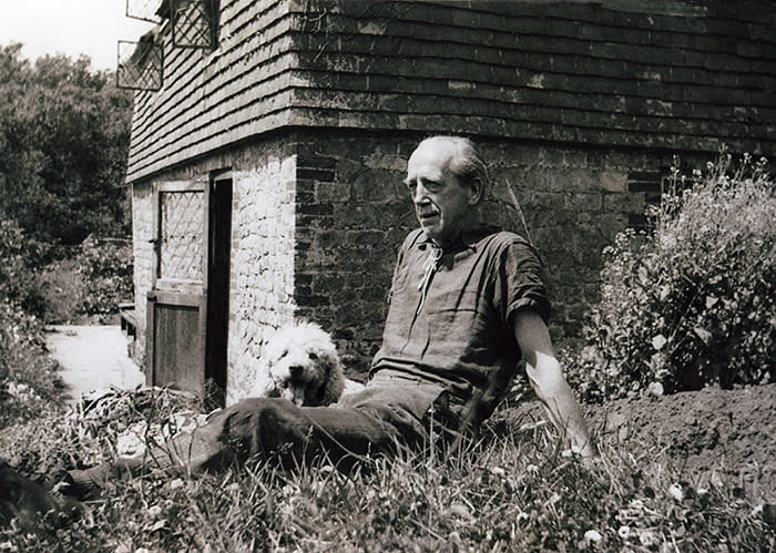Black and white photo of Max Gill sitting in a cottage garden with a white dog