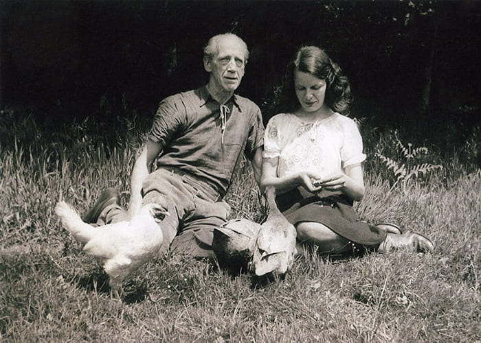 Black and white photo of Max Gill and Priscilla Johnston sitting in a garden with a chicken