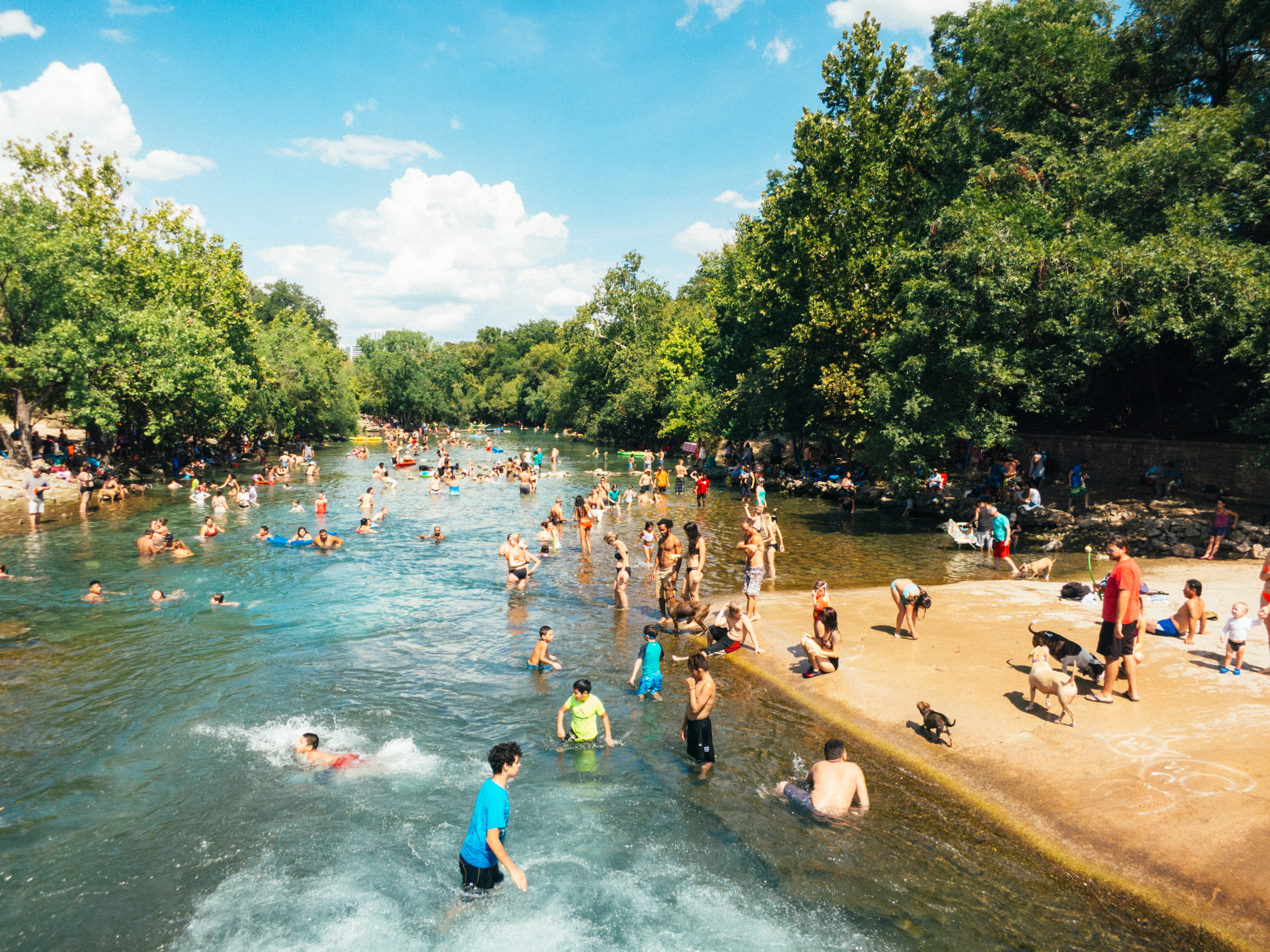 Photo of people cooling down in a river on a hot day