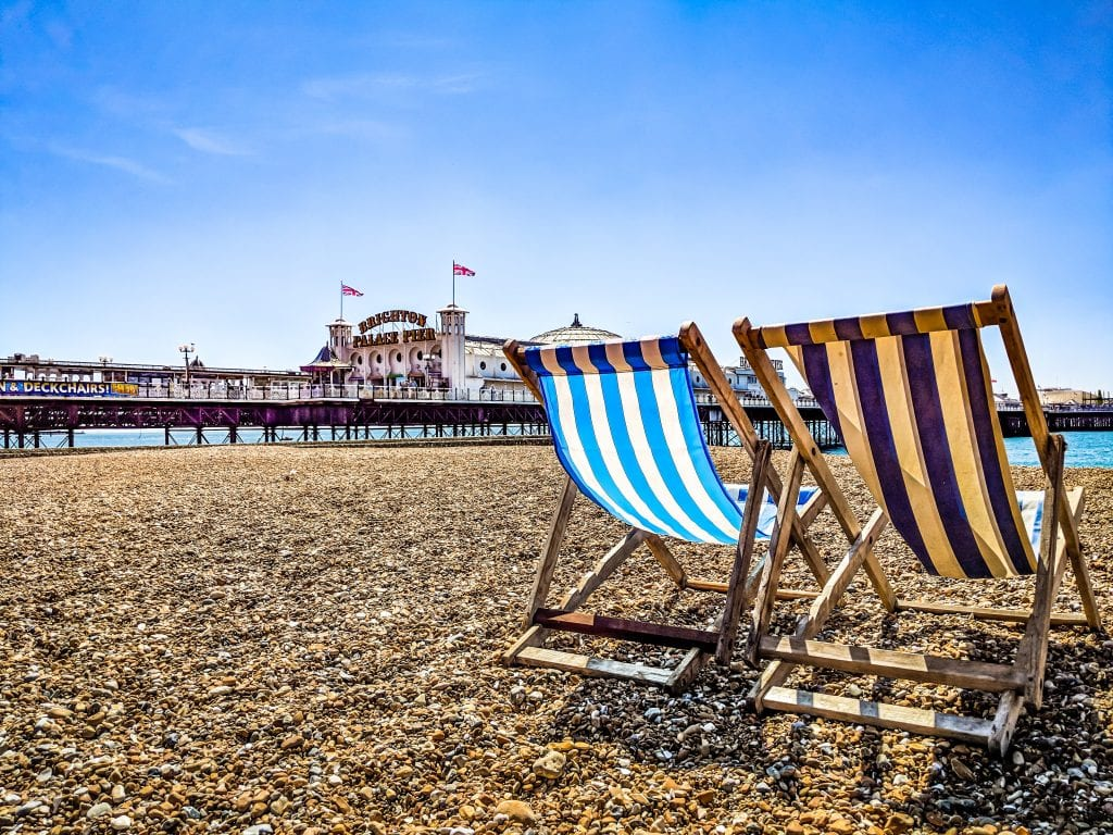 Photo of deckchairs on Brighton beach with the pier in the background