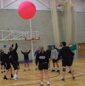 Students in the gym trying to catch the Kin-ball