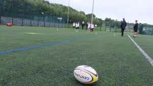 close up shot of a rugby ball with a group of children in the background