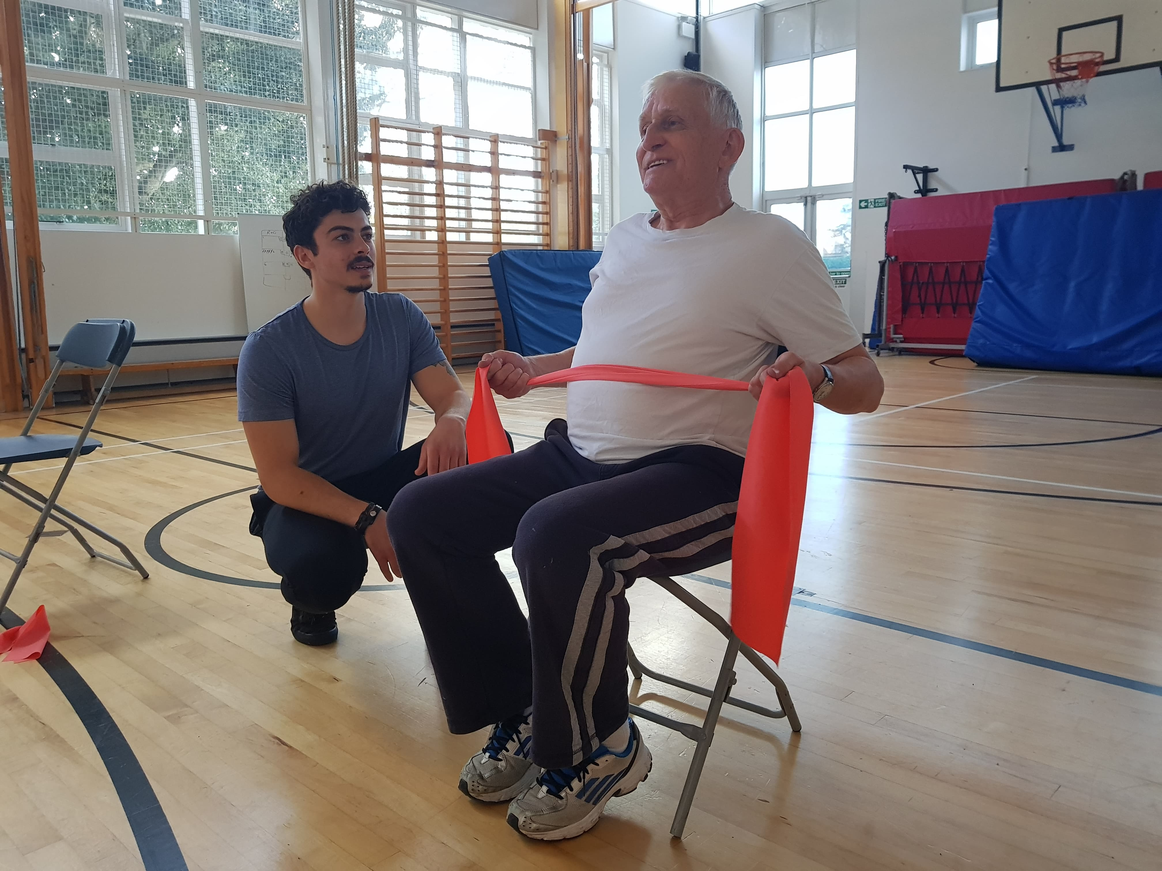 Harrison hekping Active Recovery client Paul with his exercises in the university's gym