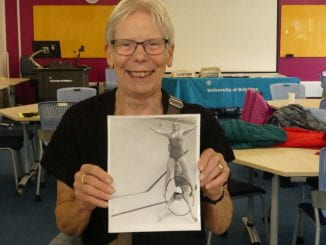 Annemarie Burgher holding a photo of herself synchronised swimmingg