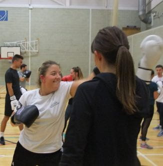 Two female students demonstrating their combat skills