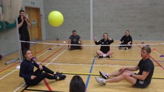Students playing sit down volley ball