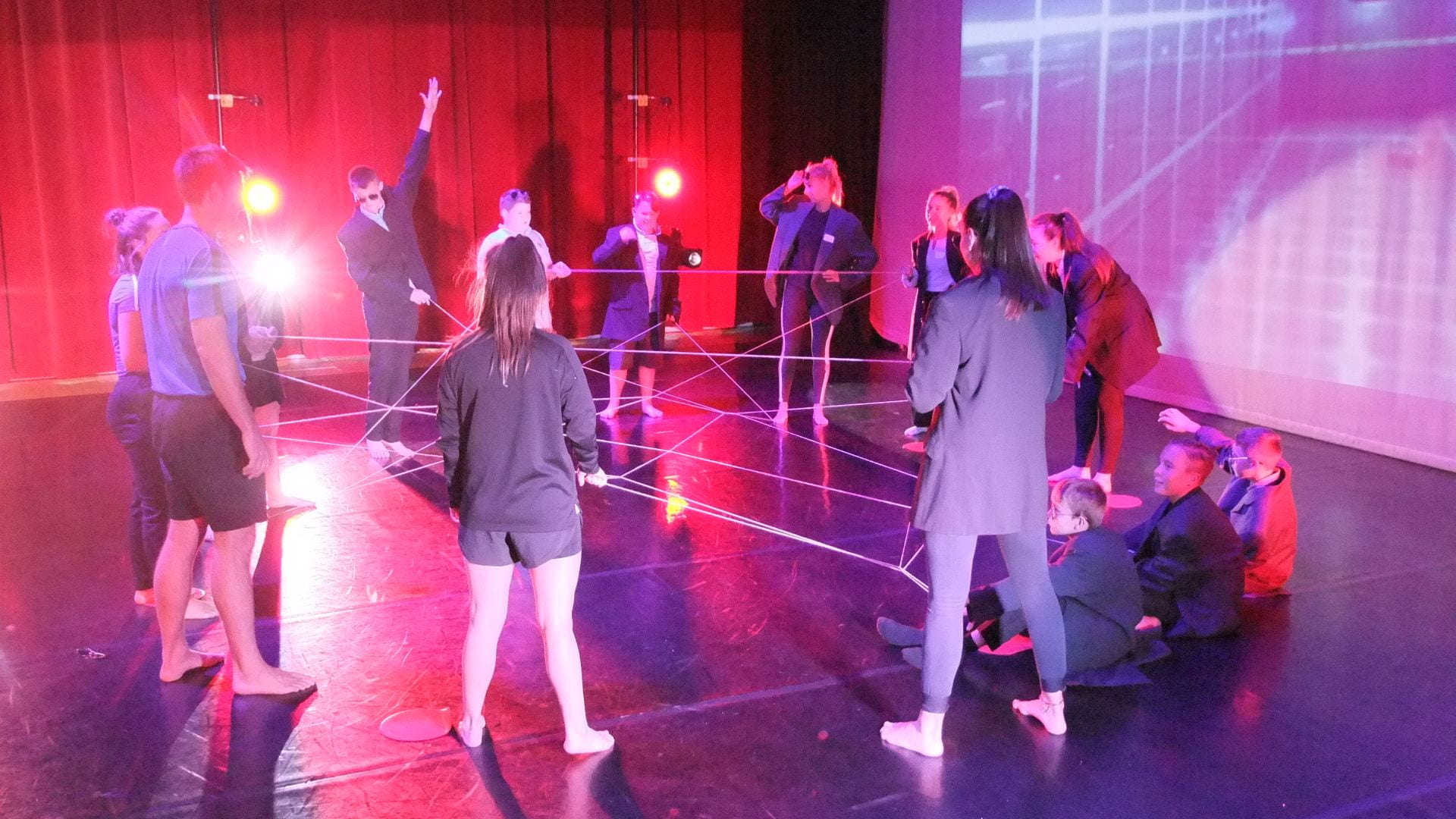 students and school pupils taking part in a dance activity