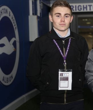 Lewis in front of the Brighton and Hove Albion FC logo