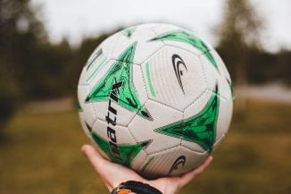 A hand holding a white football which has a green pattern on it