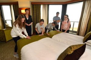 School pupils making finishing touches to making beds