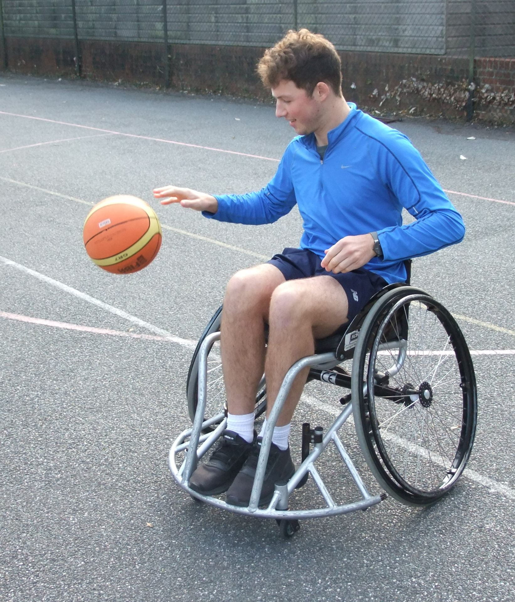 one of the students in a wheelcharir bouncing a ball