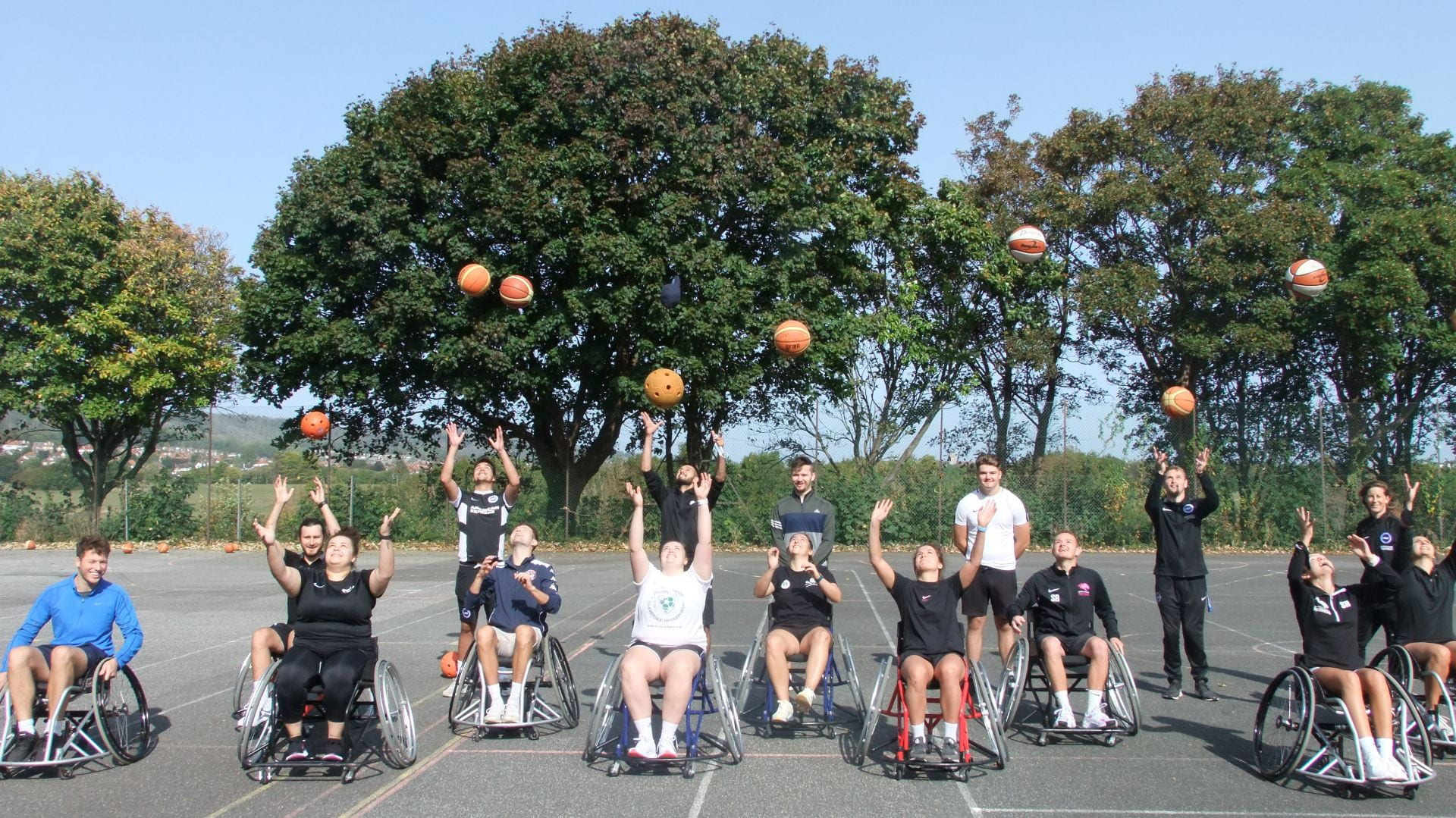 Students in wheelchairs throwing balls in the air