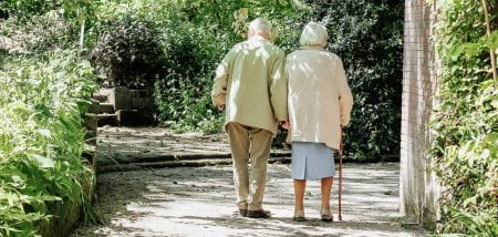an elderly couple walking in the woods