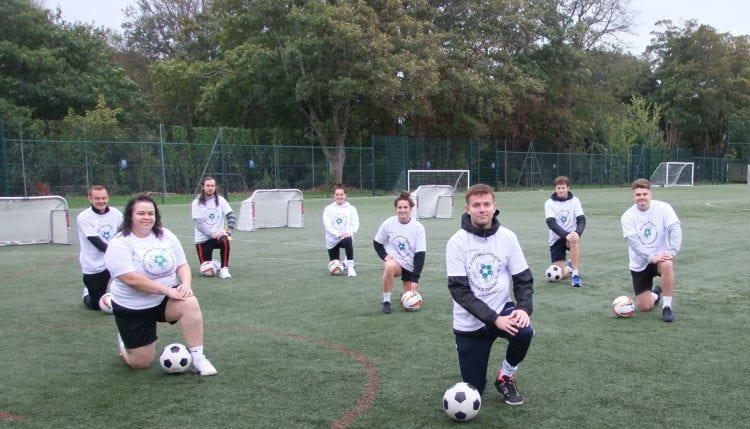 students on one knee on the football pitch