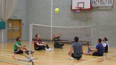 students playing sit down volleyball