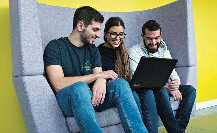 Three students sharing a laptop screen