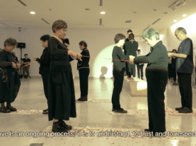 Still image of performers in passing and cutting