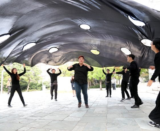Performers in black under large perforated sheet. In-Out performance, Seoul Museum of Art, Korea
