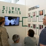 Exhibition booth with title Silver Stories on a wall, a monitor playing films and foamboards with information on project and participants in digital storytelling