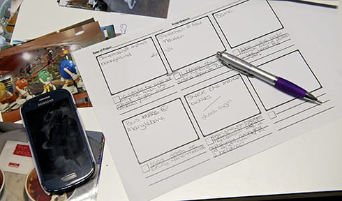 Tools of digital storytelling, a storyboard of squares and a mobile device and writing or drawing materials