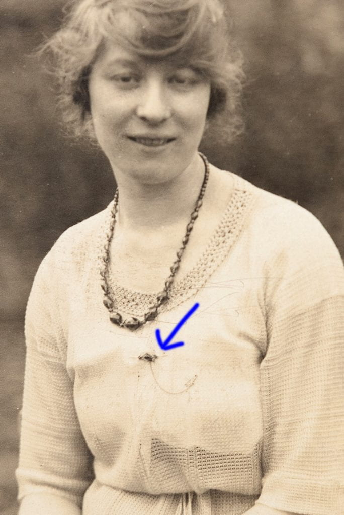 photograph of a woman wearing a broach pin with an arrow pointing out the pin on the womans top