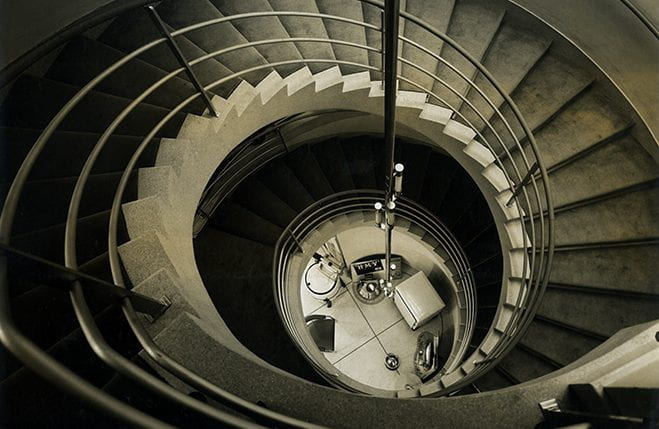 A black and white photograph showing the spiral staircase at the HMV headquarter building. Designed by Joseph Emberton. Taken from the Joseph Emberton Archive housed at the University of Brighton Design Archives.