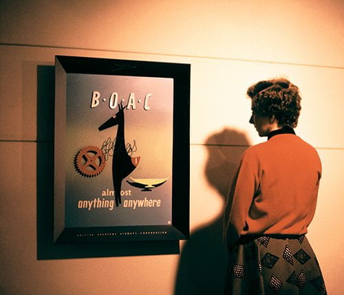Woman in orange jumper looking at a framed advertising image for BOAC at the British Design Exhibition in North America (no date), picture taken from the Willy de Majo Archive housed at the University of Brighton Design Archives.