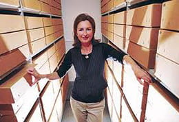 A colour photographs showing Dr Catherine Moriarty, Curatorial Director at the University of Brighton Design Archives, amongst archival boxes.
