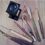 Selection of desk equipment for conservation including magnifier, tweezers and scalpels