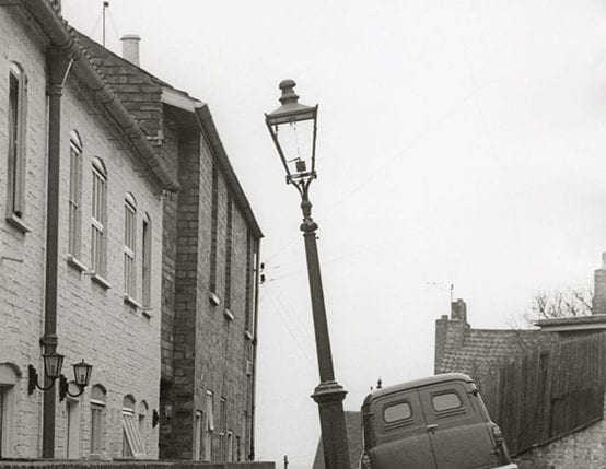 A black and white image of a car on a cobbled street next to a lamp post. Taken from the University of Brighton Design Archives.