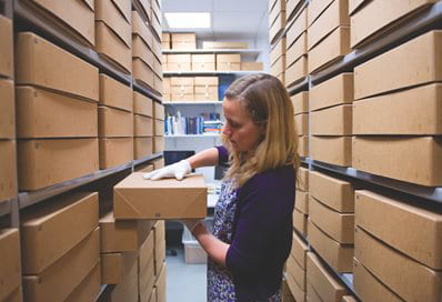 A colour photograph of Sue Breakell looking at archival boxes at the University of Brighton Design Archives