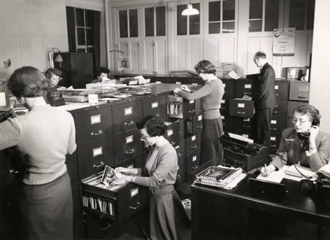 Black and white photograph of Image: Photographic Library, The Council of Industrial Design. Staff in the general office housing the duplicate prints working on requests received from callers, or through the post of telephone. Taken from the Design Council Archive housed at the University of Brighton Design Archives.