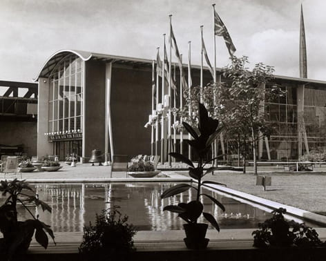 Black and white general view image from the Festival of Britain (1951), showing a pond and one of the Pavilions. From the Design Council Archive housed in the University of Brighton Design Archives.