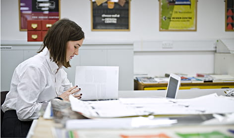 Colour photograph of Leah Armstrong doing research in the University of Brighton Design Archives