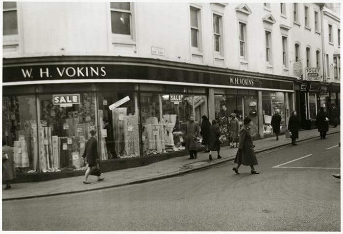 Black and white photograph of the exterior view of the Vokins Department store in Brighton (no date) with fabrics in the shop window. Taken from the Vokins Archive housed at the University of Brighton Design Archives.