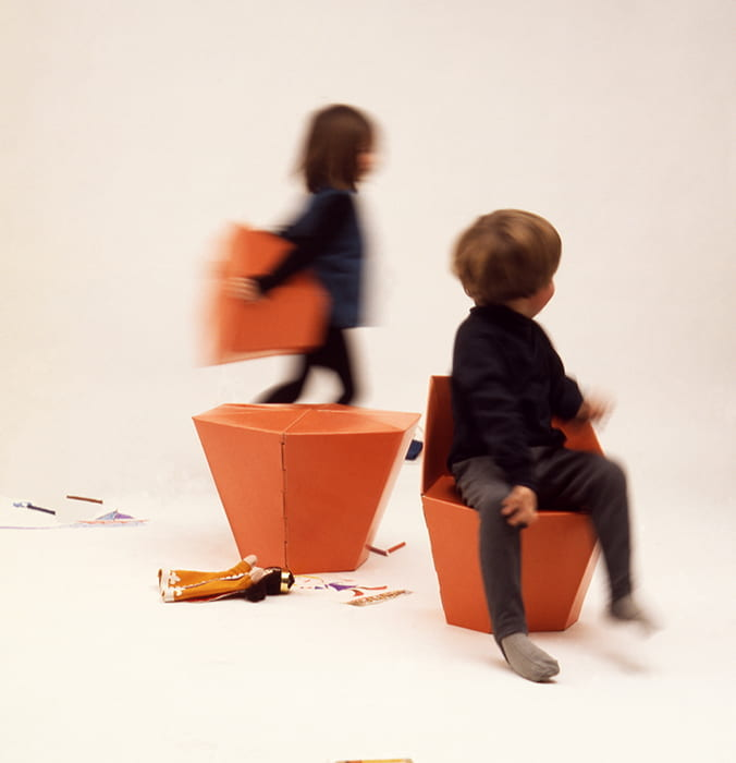 A colour photograph showing two children playing with 'Those Things': a self assembly fibreboard for children, winner of Council of Industrial Design Award in 1968. Designed by Peter Murdoch and manufactured by Perspective Designs Ltd. Taken from the Design Council Archive housed at the University of Brighton Design Archives.