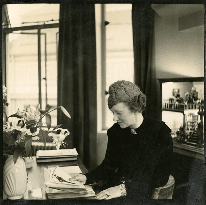 A black and white photograph of Alison Settle looking at sketches at her desk. Taken from the Alison Settle archive housed at the University of Brighton Design Archives.