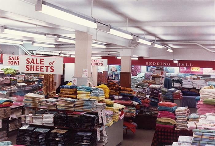 Colour photograph showing an interior view of the Vokins department store with piles of sheets on sale on display tables. Taken from the Vokins Archive housed at the University of Brighton Design Archives.