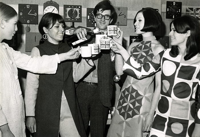 A black and white photograph of Paul Clark making a toast with four women (no date). Taken from the Paul Clark Archive housed at the University of Brighton Design Archives.