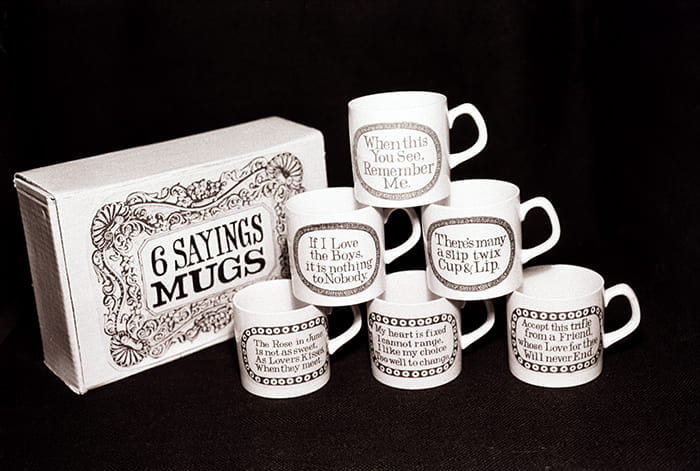 A photograph showing all of Paul Clark's '6 Sayings Mugs' in a pyramid formation with the original box beside them. Taken from the Paul Clark Archive housed at the University of Brighton Design Archives.