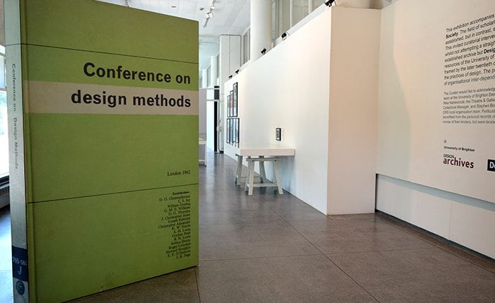 Gallery view showing giant green book titled 'Conference on design methods' on left side of image. The right side shows exhibition test , display table and framed images on the wall.