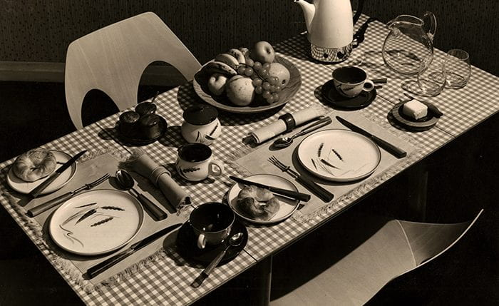 A breakfast table setting for two, which is part of the 'Britain at Table' display in The Design Centre, July - September, 1956. Formica-topped table, two stacking chairs 'Jason', Irish linen tablemats and napkins. 'Green Wheat' stoneware. Electric coffee percolator. Water jug and glasses. Cutlery and flatware with walnut handles.